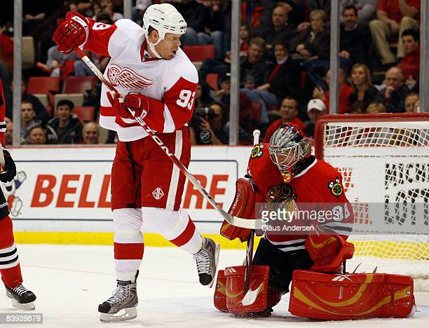 Johan Franzen of the Detroit Red Wings tips a shot at Cristobal Huet of the Chicago Blackhawks in a game on December 6 2008 at the Joe Louis Arena in...
