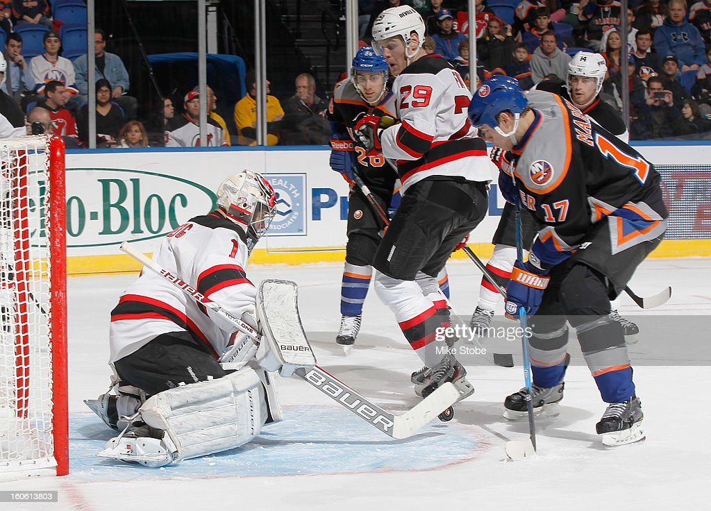 Johan Hedberg #1 and Mark Fayne #29 of the New Jersey Devils defend the net against Matt Martin #17 of the New York Islanders at Nassau Veterans Memorial Coliseum on February 3, 2013 in Uniondale, New York. The Devils defeat the Islanders 3-0.