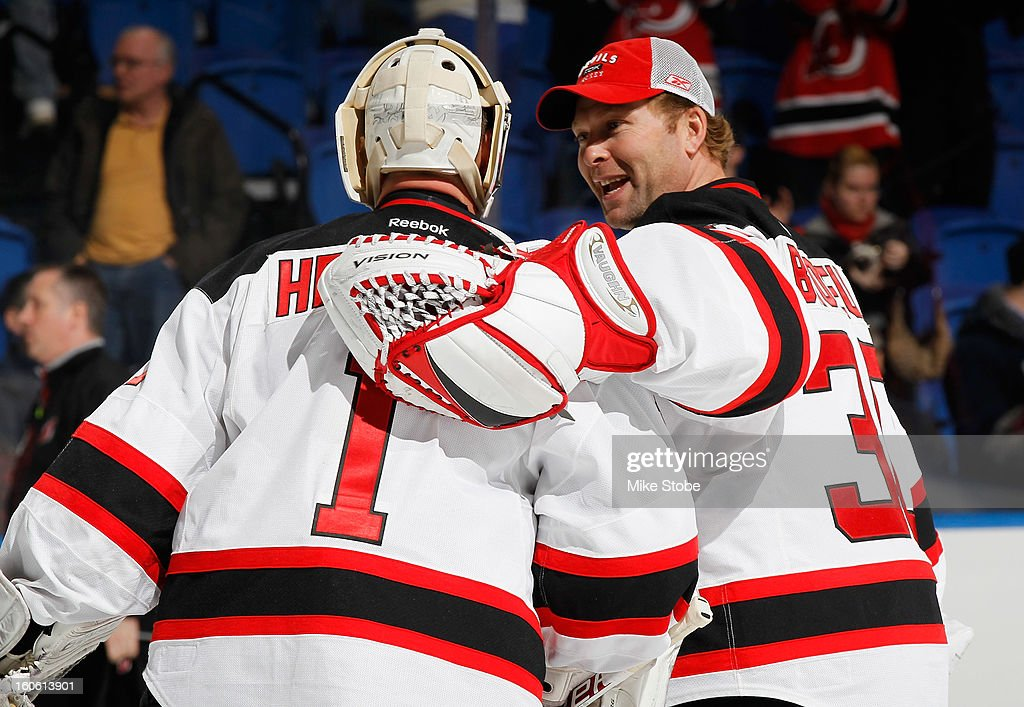 Johan Hedberg #1 of the New Jersey Devils is congradulated by teammate Martin Brodeur #30 after defeating the New York Islanders at Nassau Veterans Memorial Coliseum on February 3, 2013 in Uniondale, New York. The Devils defeat the Islanders 3-0.