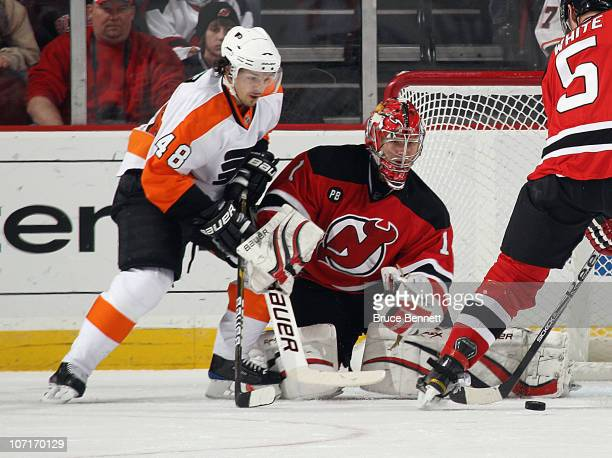 Johan Hedberg of the New Jersey Devils keeps his eye on the puck as Danny Briere of the Philadelphia Flyers looks for a rebound at the Prudential...