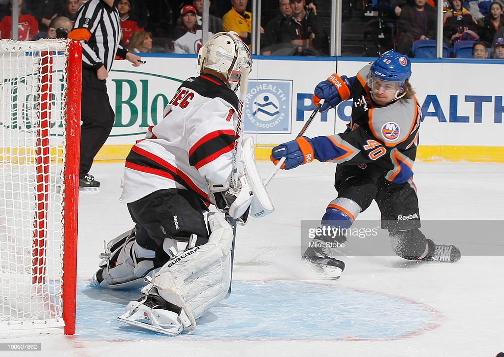 Johan Hedberg #1 of the New Jersey Devils makes a save against Michael Grabner #40 of the New York Islanders at Nassau Veterans Memorial Coliseum on February 3, 2013 in Uniondale, New York.