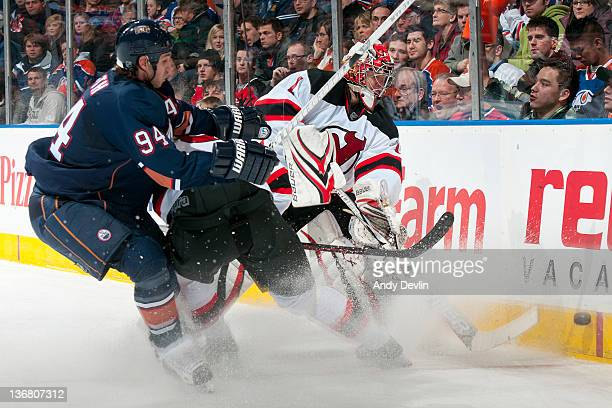 Johan Hedberg of the New Jersey Devils plays the puck away from a forechecking Ryan Smyth of the Edmonton Oilers at Rexall Place on January 11 2012...