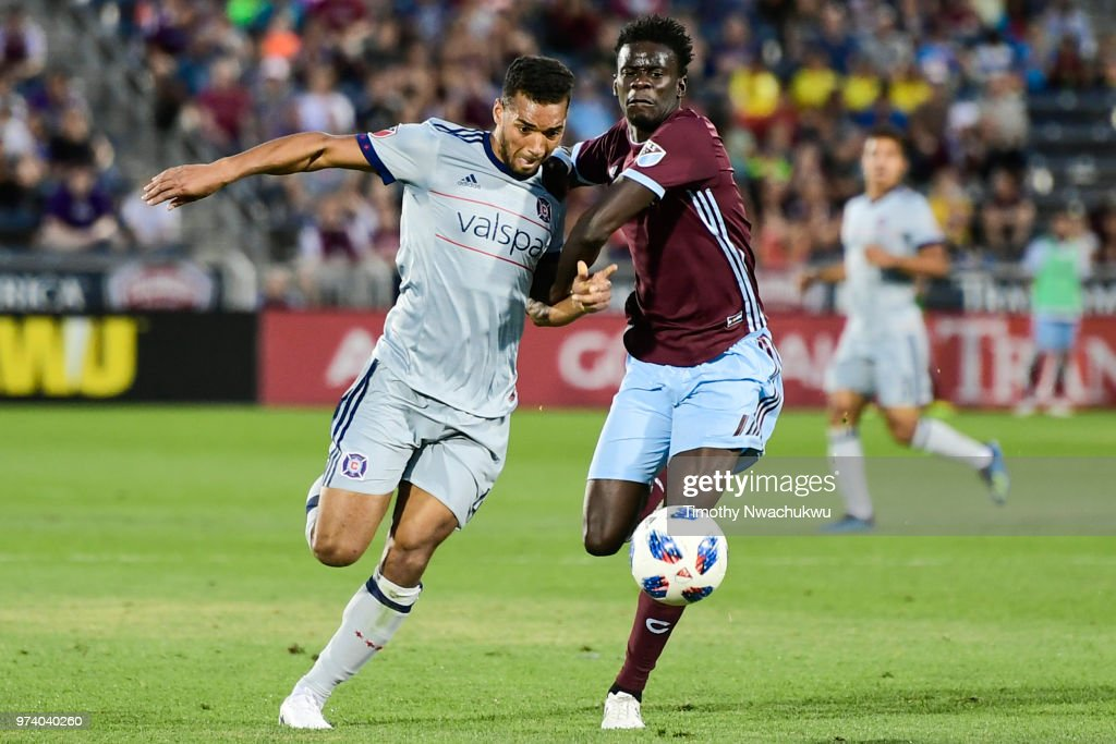 Johan Kappelhof #4 of Chicago Fire and Dominique Badji #14 of Colorado Rapids chase a loose ball at Dick's Sporting Goods Park on June 13, 2018 in Commerce City, Colorado.