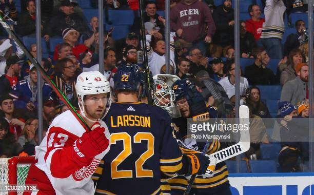 Johan Larsson and Jake McCabe congratulates Carter Hutton of the Buffalo Sabres as Darren Helm of the Detroit Red Wings skates away following an NHL...