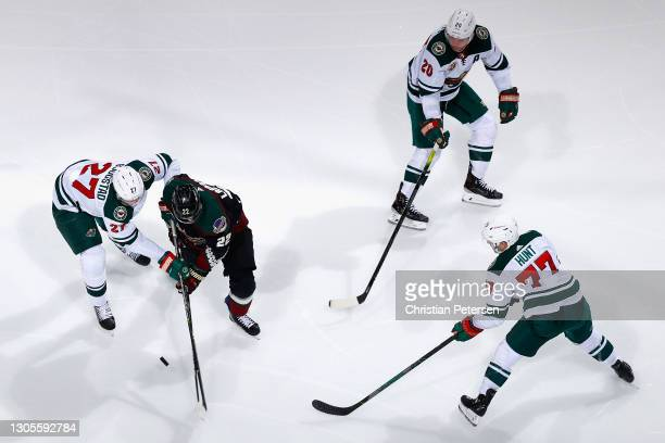 Johan Larsson of the Arizona Coyotes skates with the puck against Nick Bjugstad, Brad Hunt and Ryan Suter of the Minnesota Wild during the third...