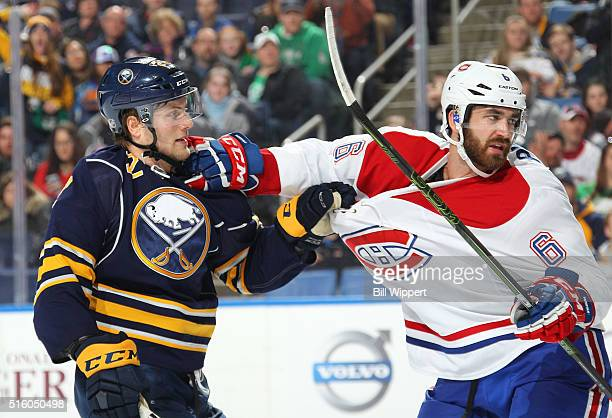 Johan Larsson of the Buffalo Sabres hangs on during a second period scuffle against Greg Pateryn of the Montreal Canadiens during an NHL game on...