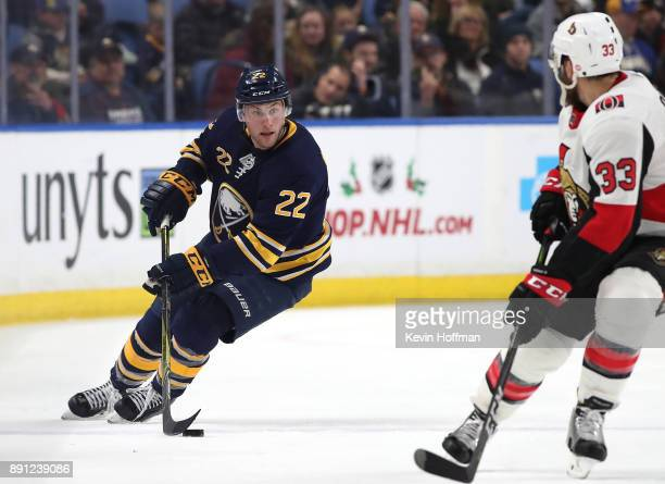 Johan Larsson of the Buffalo Sabres skates up ice with the puck as Fredrik Claesson of the Ottawa Senators defends during the second period at the...