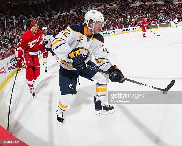 Johan Larsson of the Buffalo Sabres skates with the puck as Danny DeKeyser of the Detroit Red Wings gives chase during an NHL game at Joe Louis Arena...