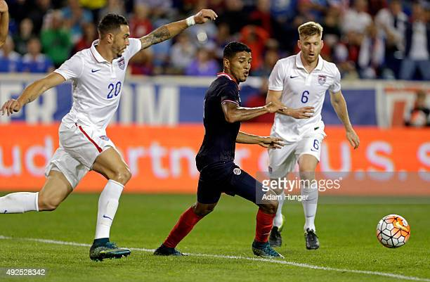 Johan Venegas of Costa Rica chases a loose ball against Geoff Cameron of the United States and Tim Ream of the United States during the first half at...