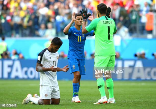 Johan Venegas of Costa Rica prays while Philippe Coutinho of Brazil celebrates victory with teammate Alisson folowing the 2018 FIFA World Cup Russia...