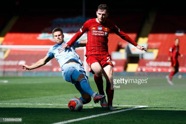 Johann Berg Gudmundsson of Burnley and Andy Robertson of Liverpool clash during the Premier League match between Liverpool FC and Burnley FC at...