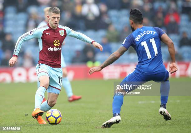 Johann Gudmundsson of Burnley is challenged by Theo Walcott of Everton during the Premier League match between Burnley and Everton at Turf Moor on...