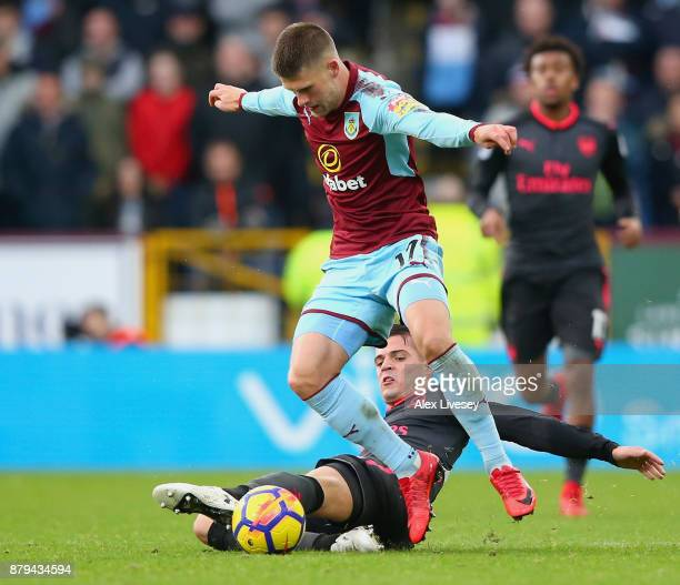 Johann Gudmundsson of Burnley is tackled by Granit Xhaka of Arsenal during the Premier League match between Burnley and Arsenal at Turf Moor on...