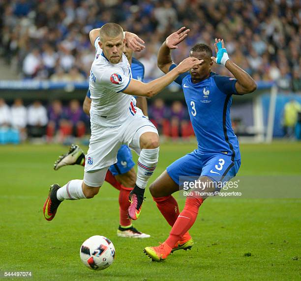 Johann Gudmundsson of Iceland is challenged by Patrice Evra of France during the UEFA EURO 2016 quarter final match between France and Iceland at...