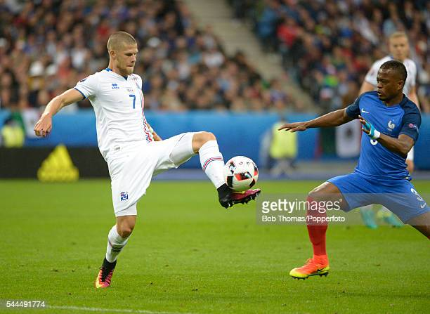 Johann Gudmundsson of Iceland with Patrice Evra of France during the UEFA EURO 2016 quarter final match between France and Iceland at Stade de France...