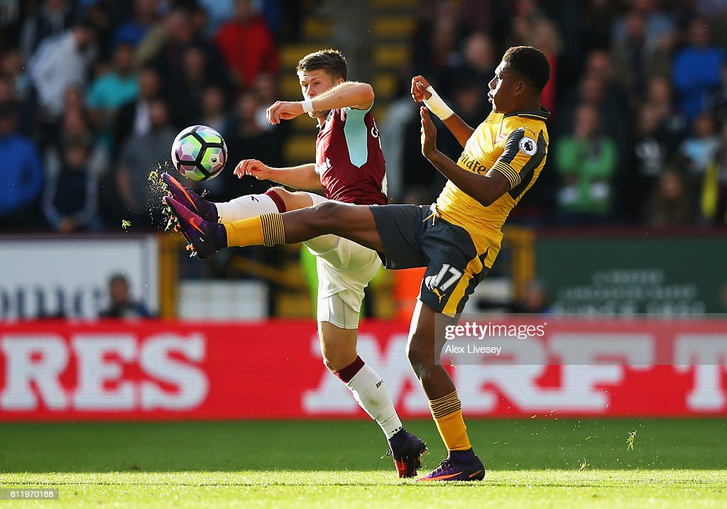Johann Guomundsson of Burnley (L) and Alex Iwobi of Arsenal (R) battle for possession during the Premier League match between Burnley and Arsenal at Turf Moor on October 2, 2016 in Burnley, England.