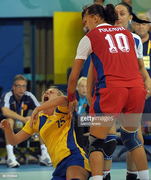 Johanna Ahlm of Sweden collaps after clashing against Elena Polenova of Russia during their 2008 Olympics Games women's Handball match on August 11...