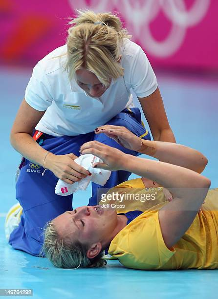 Johanna Ahlm of Sweden is attended to after injuring herself during the Women's Handball Preliminaries Group A match between Spain and Sweden on Day...