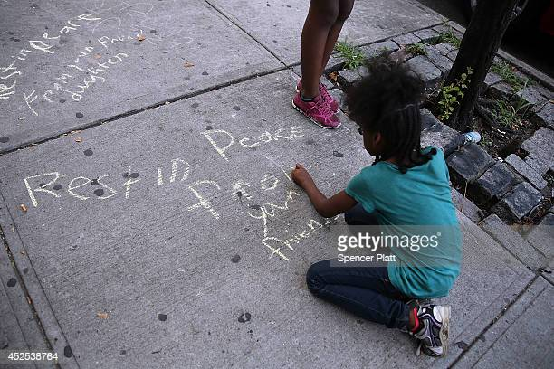 Johanna Fuentes draws a message for Eric Garner near where he died after he was taken into police custody in Staten Island last Thursday on July 22...