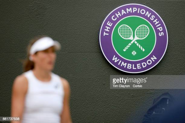 Johanna Konta of Great Britain stood in front of the Wimbledon emblem during her match against Caroline Garcia of France in the Ladies' Singles round...