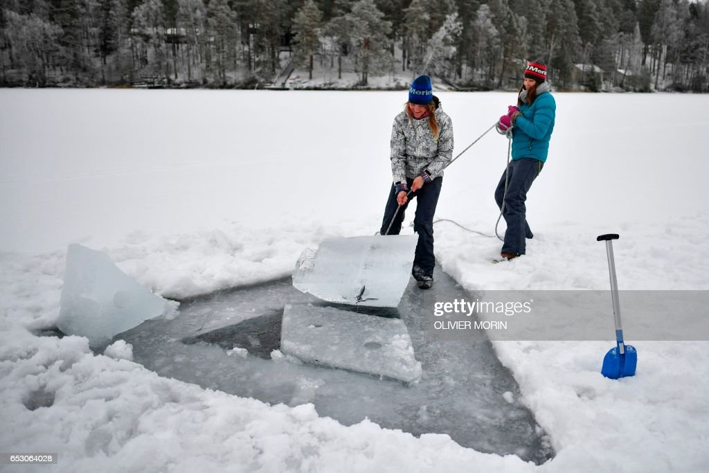 Johanna Nordblad (L) , 42, Finnish freediver and her sister Elina, remove ice from a frozen lake in order to train Ice-freediving on February 27, 2017, in Somero (southwest Finland). The ice is about 45cm thick, water temperature +1°C. Johanna Nordblad holds the world record of freediving under ice with bathing suit with 50m distance. / AFP PHOTO / OLIVIER MORIN / TO GO WITH AFP STORY BY Sabine COLPART