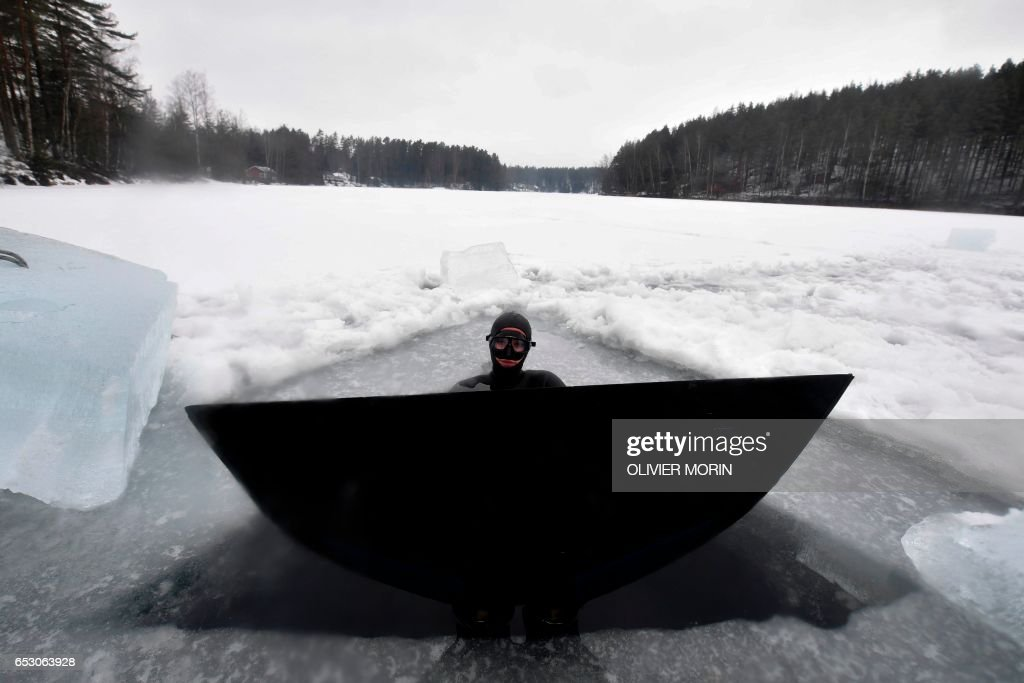 Johanna Nordblad, 42, Finnish freediver gets concentrated before Ice-freediving training session on February 28, 2017, in a green lake in Somero (southwest Finland). The ice is about 45cm thick, water temperature +1°C. Johanna Nordblad holds the world record of freediving under ice with bathing suit with 50m distance. / AFP PHOTO / OLIVIER MORIN / TO GO WITH AFP STORY BY Sabine COLPART