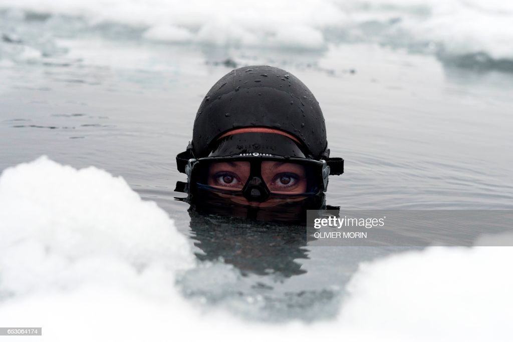Johanna Nordblad, 42, Finnish freediver looks up from the water during a Ice-freediving training session on February 28, 2017, in Somero (southwest Finland). The ice is about 45cm thick, water temperature +1°C. Johanna Nordblad holds the world record of freediving under ice with bathing suit with 50m distance. / AFP PHOTO / OLIVIER MORIN / TO GO WITH AFP STORY BY Sabine COLPART