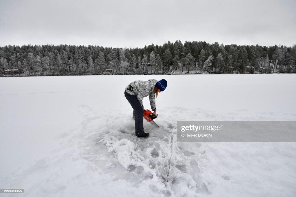Johanna Nordblad, 42, Finnish freediver makes a hole with a chainsaw in a frozen lake in order to train Ice-freediving on February 27, 2017, in Somero (southwest Finland). The ice is about 45cm thick, water temperature +1°C. Johanna Nordblad holds the world record of freediving under ice with bathing suit with 50m distance. / AFP PHOTO / OLIVIER MORIN / TO GO WITH AFP STORY BY Sabine COLPART