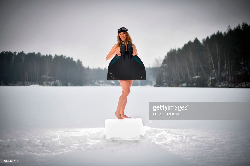 Johanna Nordblad, 42, Finnish freediver poses with her monofin on a frozen lake in order to train Ice-freediving training session on February 27, 2017, in Somero (southwest Finland). The ice is about 45cm thick, water temperature +1°C. Johanna Nordblad holds the world record of freediving under ice with bathing suit with 50m distance. / AFP PHOTO / OLIVIER MORIN / TO GO WITH AFP STORY BY Sabine COLPART