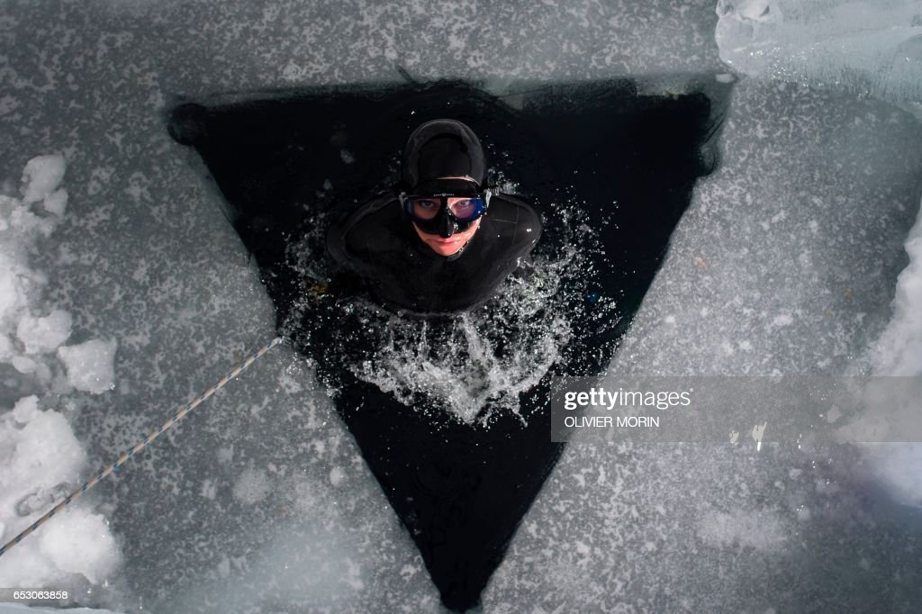 Johanna Nordblad, 42, Finnish freediver swims out from under the ice during a a Ice-freediving training session on February 28, 2017, in Somero (southwest Finland). The ice is about 45cm thick, water temperature +1°C. Johanna Nordblad holds the world record of freediving under ice with bathing suit with 50m distance. / AFP PHOTO / OLIVIER MORIN / TO GO WITH AFP STORY BY Sabine COLPART