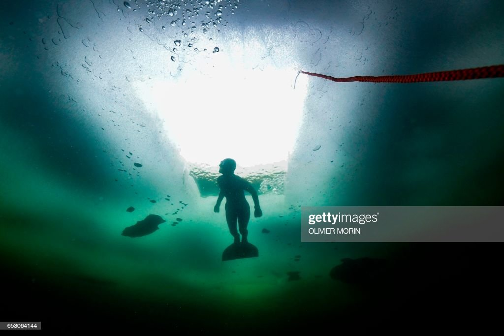 Johanna Nordblad, 42, Finnish freediver swims under ice during a Ice-freediving training session on February 28, 2017, in a green lake in Somero (southwest Finland). The ice is about 45cm thick, water temperature +1°C. Johanna Nordblad holds the world record of freediving under ice with bathing suit with 50m distance. / AFP PHOTO / OLIVIER MORIN / TO GO WITH AFP STORY BY Sabine COLPART