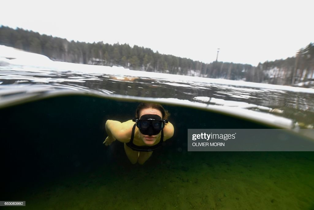 Johanna Nordblad, 42, Finnish freediver swims under Ice layer in a bathing suit during an Ice-freediving training session on February 28, 2017, in a green lake in Somero (southwest Finland). The ice is about 45cm thick, water temperature +1°C. Johanna Nordblad holds the world record of freediving under ice with bathing suit with 50m distance. / AFP PHOTO / OLIVIER MORIN / TO GO WITH AFP STORY BY Sabine COLPART