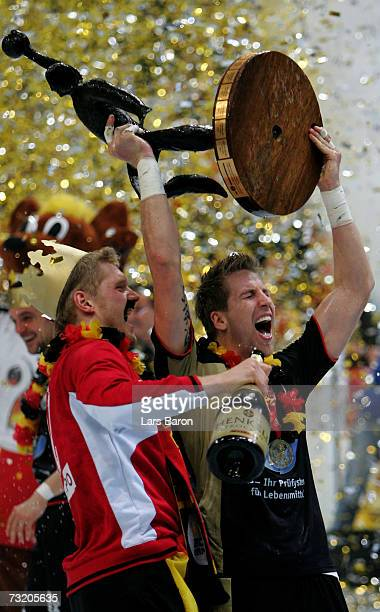 Johannes Bitter and Oliver Roggisch lift the caup after winning the IHF World Championship final game between Germany and Poland at the Cologne Arena...