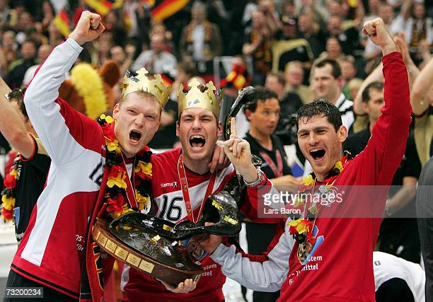 Johannes Bitter, Christian Lichtlein and Henning Fritz of Germany celebrate with the cup after winning the IHF World Championship final between...