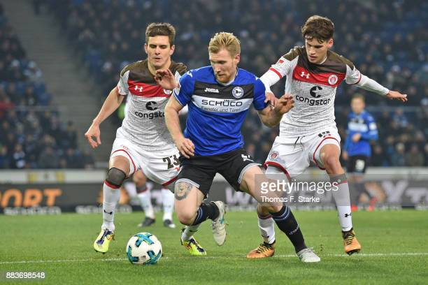 Johannes Flum and Luca Zander of St Pauli tackle Andreas Voglsammer of Bielefeld during the Second Bundesliga match between DSC Arminia Bielefeld and...
