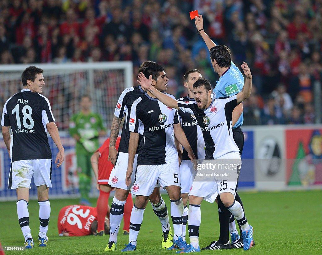 Johannes Flum of Frankfurt (L) is shown the red card from by referee Deniz Aytekin during the Bundesliga match between SC Freiburg and Eintracht Frankfurt at Mage Solar Stadium on October 6, 2013 in Freiburg, Germany. Tranquillo Barnetta of Frankfurt in front reacts.