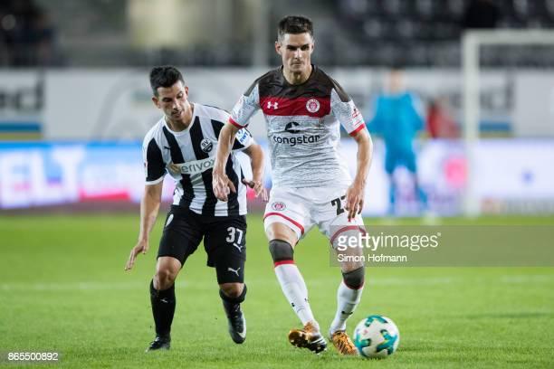 Johannes Flum of St Pauli is challenged by JulianMaurice Derstroff of Sandhausen during the Second Bundesliga match between SV Sandhausen and FC St...