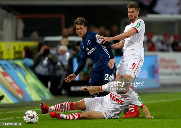 Johannes Geis and Simon Terodde of Koeln challenge Gotoku Sakai of Hamburg during the Second Bundesliga match between 1 FC Koeln and Hamburger SV at...