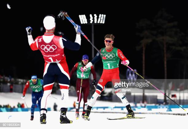 Johannes Hoesflat of Norway celebrates as he crosses the finish line to win gold with team mate Martin Johnsrud Sundby of Norway during the Cross...
