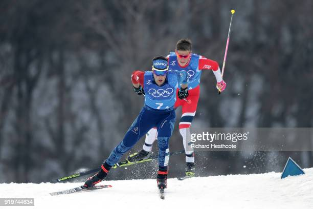 Johannes Hoesflot Klaebo of Norway and Adrien Backscheider of France compete in the final leg during CrossCountry Skiing men's 4x10km relay on day...