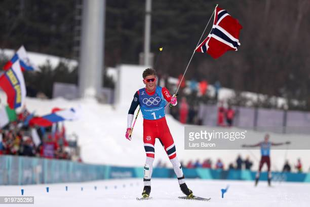 Johannes Hoesflot Klaebo of Norway celebrates after crossing the finish line to win the gold medal during CrossCountry Skiing men's 4x10km relay on...