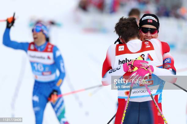 Johannes Hoesflot Klaebo of Norway embraces Emil Iversen of Norway following their victory in the Mens' Cross Country Team Sprint during FIS Nordic...
