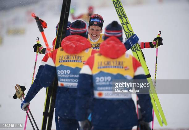 Johannes Hoesflot Klaebo of Norway is greeted by team mates as he crosses the finish line in first place during the Men's Cross Country 4x10 km Relay...