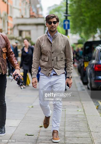 Johannes Huebel wearing a beige jacket and white pants outside Coach during The London Collections Men SS17 on June 13 2016 in London England