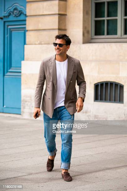 Johannes Huebl, wearing a white t-shirt, beige blazer, blue jeans and brown loafers, is seen outside Dundas show during Paris Fashion Week - Haute...