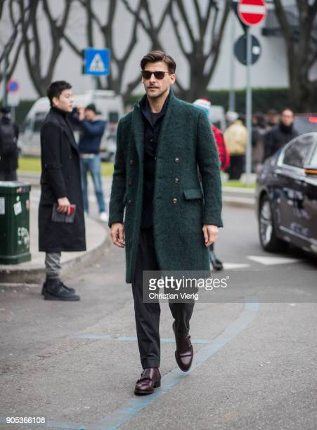 Johannes Huebl wearing dark green wool coat navy jacket with high collar is seen outside Armani during Milan Men's Fashion Week Fall/Winter 2018/19...