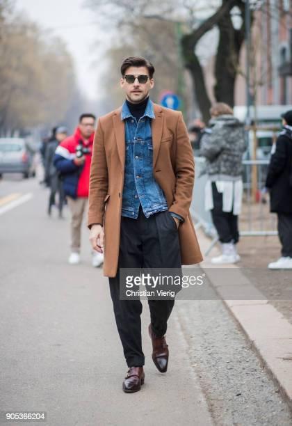Johannes Huebl wearing denim jacket brown wool coat black wide leg pants brown leather shoes is seen outside Fendi during Milan Men's Fashion Week...