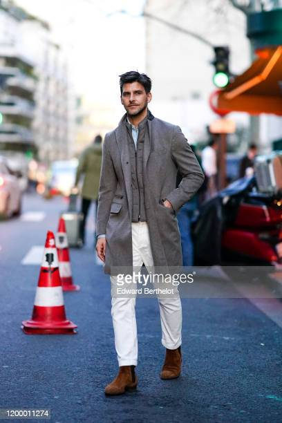 Johannes Huebl wears a gray long jacket, a shirt, white pants, brown suede shoes, outside Rochas, during Paris Fashion Week - Menswear Fall / Winter...