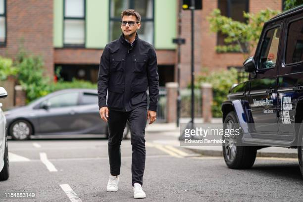 Johannes Huebl wears sunglasses, a black jacket with several pockets, black pants, white sneakers shoes, during London Fashion Week Men's June 2019...