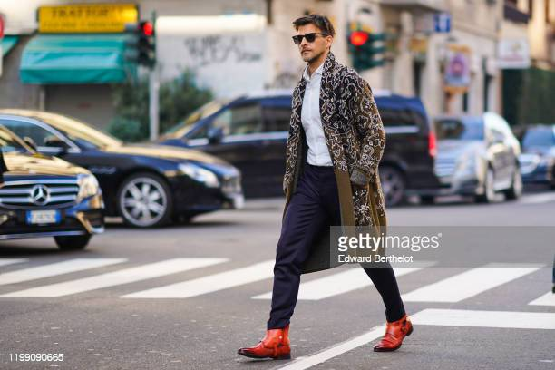 Johannes Huebl wears sunglasses, a shirt, dark blue pants, brown leather pointy shoes, a green khaki long wool jacket with printed geometric...
